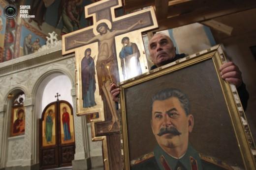 GEO106 GORI (GEORGIA) 05/03/2013.- Un hombre porta un retrato del exdictador soviÈtico Joseph Stalin durante una misa celebrada con motivo del aniversario de la muerte de Stalin en una iglesia en Gori, a unos 80km de Tbilisi hoy, martes 5 de marzo de 2013. EFE/ Zurab Kurtsikidze
